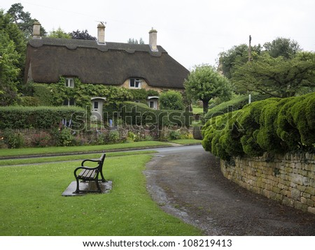 Beautiful old cottage with thatched roof and great hedges in the village of Chipping Campden, Cotswold, United Kingdom. - stock photo