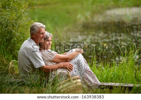 Beautiful old couple sitting in the grass near the lake. Vintage photo - stock photo