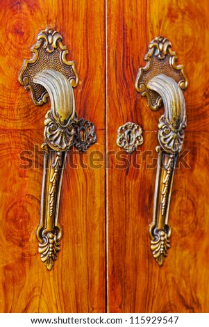 Beautiful old door handles on a cupboard - stock photo