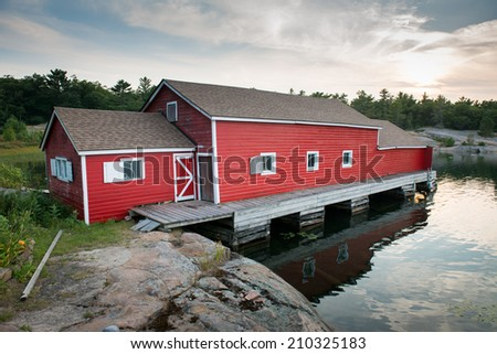 Beautiful old, red boat house with blue sky, green grass and rocky shore - stock photo