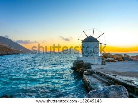 Beautiful old traditional windmill by the port of Aigiali village in Amorgos island in Greece - stock photo