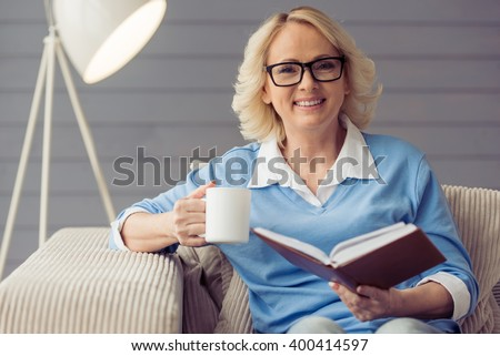 Beautiful old woman in casual clothes and glasses is reading a book, holding a cup and smiling while sitting in armchair at home - stock photo