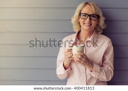 Beautiful old woman in classic shirt and glasses is holding a cup, looking at camera and smiling, standing against gray background - stock photo