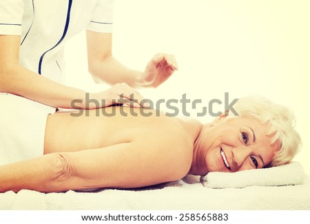 Beautiful old woman is having a massage. - stock photo