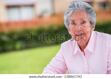 Beautiful old woman relaxing outdoors and looking happy - stock photo