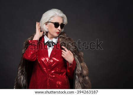 Beautiful old woman with blond hair wearing sunglasses. Fashionable lady in red business suit and expensive fur coat looking like Devil wears Prada. - stock photo