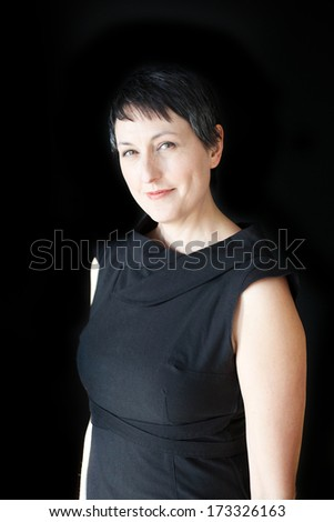 Beautiful older woman with short brown hair and eyes on a black background. - stock photo