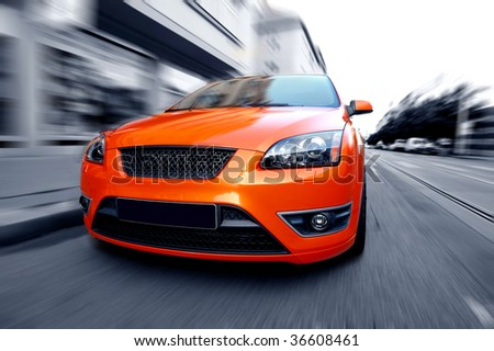 Beautiful orange sport car on the street - stock photo