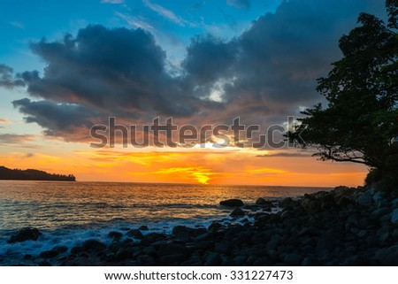 Beautiful orange sunset with blue sky and clouds on a tranquil rocky coastal beach - stock photo