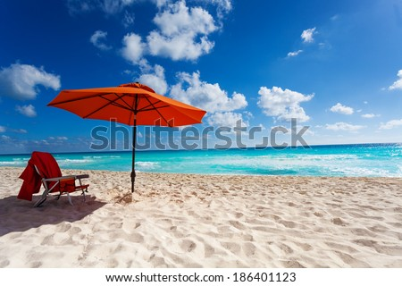 Beautiful orange umbrella and chair on the white sand beach - stock photo