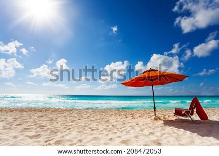 Beautiful orange umbrella panorama on the white sand beach resort with sun bright in the sky - stock photo