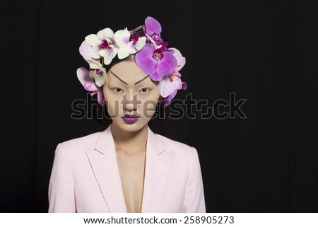 Beautiful Oriental Girl with Orchid Flowers - stock photo