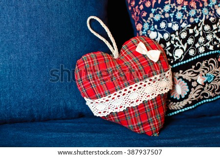 Beautiful original red heart lies on a blue couch - stock photo