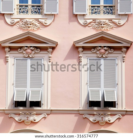 Beautiful ornate pink house with old french grey shutter windows in Principality of Monaco, Monte Carlo. Square toned image - stock photo