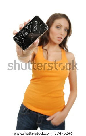 Beautiful, out of focus, young woman holding out her broken touch screen mobile phone - stock photo