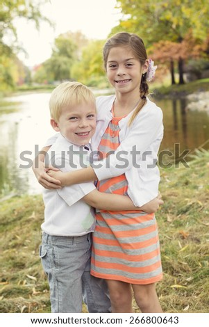 Beautiful outdoor portrait of a cute boy and girl with a scenic fall background - stock photo