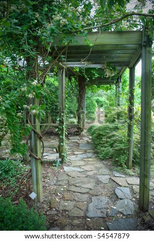 Beautiful over grown wooden pergola in lush garden settings - stock photo