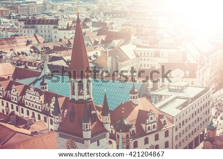 Beautiful Overview of City of Munich with Old City Hall in Foreground, as seen from Marienplatz Square on Sunny Day with Bright Sunshine and Haze - stock photo