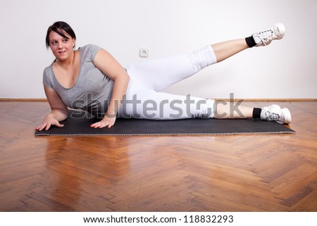 Beautiful overweight woman exercising - stock photo