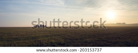 Beautiful panorama of a delicate dawn or sunset with the sun low on the horizon over open grassland countryside with a distant hills - stock photo