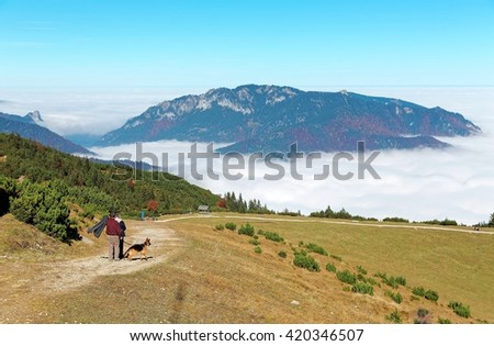 Beautiful panorama of mountains above sea of clouds and tourists with their pet dog hiking on the meadows on top of Mount Wank in Garmisch Partenkirchen, Bavaria, Germany - stock photo
