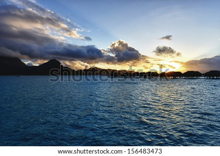Beautiful panorama of tropical sunset with water villas - stock photo