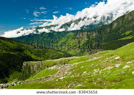 Beautiful panoramic landscape. Majestic Himalayas background with mountains, green meadows and white clouds. - stock photo