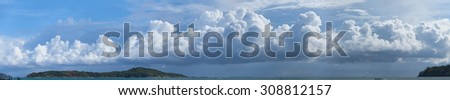 Beautiful panoramic shot of huge, billowing storm clouds, building and forming over the tropical sea near a popular tourist beach. - stock photo