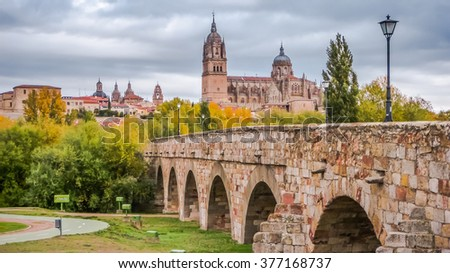 Beautiful panoramic view of the historic city of Salamanca with famous Roman bridge near Rio Tormes and New Cathedral in autumn, Castilla y Leon region, Spain - stock photo