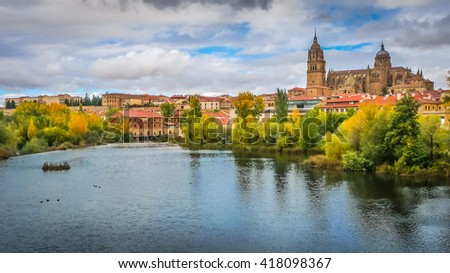 Beautiful panoramic view of the historic city of Salamanca with Rio Tormes and New Cathedral from Enrique Esteban bridge in autumn, Castilla y Leon region, Spain - stock photo