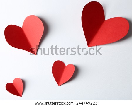 Beautiful paper hearts on white paper background, close-up - stock photo