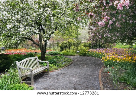 beautiful park setting with bench, flowers, trees and path - stock photo