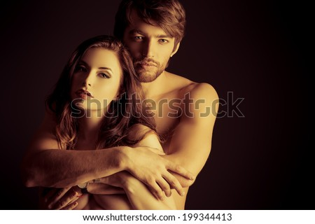 Beautiful passionate naked couple in love. Over black background. - stock photo