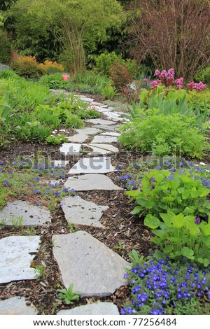 Beautiful paved stone walkway in a spring garden. - stock photo