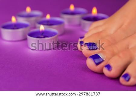 Beautiful pedicure close-up. Beautiful toenails. Purple manicure. Nail care legs. - stock photo