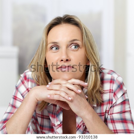 beautiful pensive blond woman at home on sofa - stock photo
