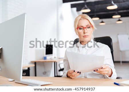 Beautiful pensive mature businesswoman reading papers in office - stock photo