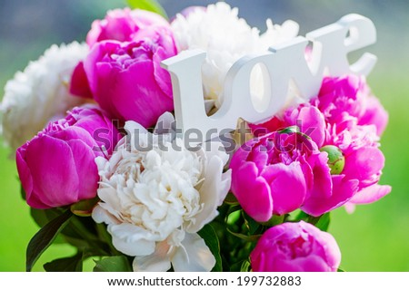 Beautiful peonies with word Love - stock photo