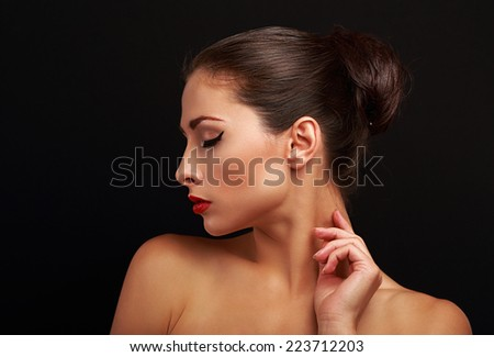 Beautiful perfect makeup model with elegant hairstyle touching health skin on black background - stock photo