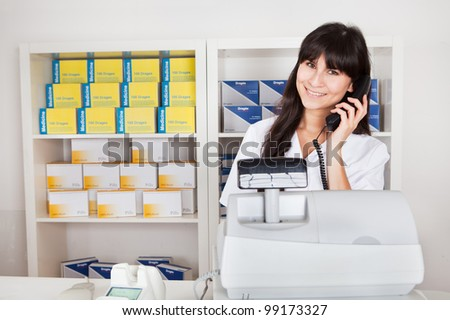 Beautiful pharmacist at the drugstore calling on the phone - stock photo