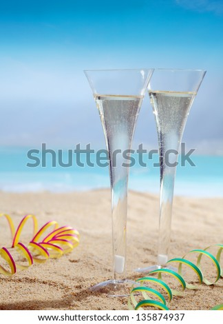 Beautiful photo composition of glasses of champagne on the beach. - stock photo