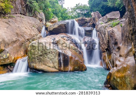 Beautiful photo of waterfalls with soft flowing water and large colored rocks. Green wild jungles on background. - stock photo