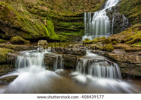 Beautiful picturesque Scaleber Force Waterfall in the Yorkshire Dales National Park with two small cascading falls in the foreground. - stock photo