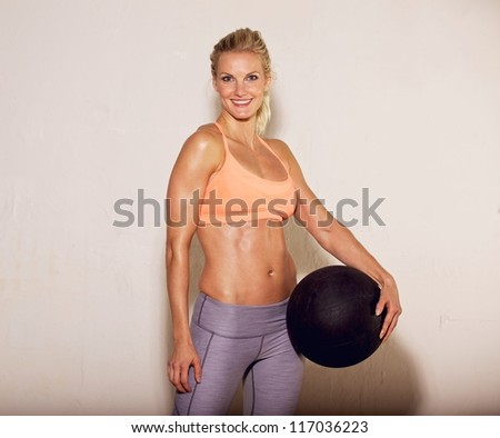 Beautiful pilates instructor holding a fitness ball - stock photo