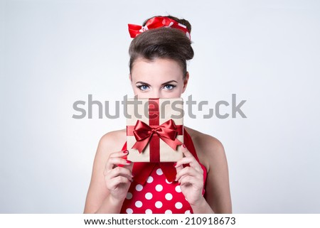 Beautiful pin-up girl holding gift box with red ribbon bow - stock photo