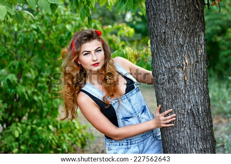 Beautiful pin-up girl in denim overalls and a a red kerchief hiding behind a tree - stock photo