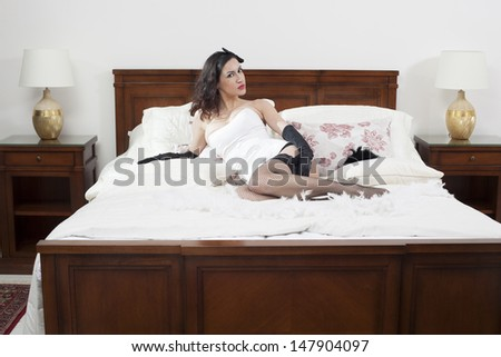 Beautiful pin-up girl on a double bed - stock photo