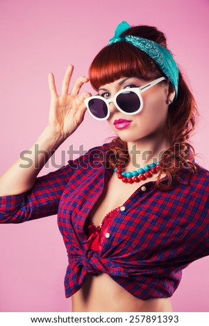 beautiful pin-up girl posing with red heart-shaped lollipop against pink background - stock photo