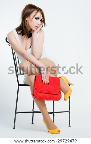 Beautiful pin-up girl with red bag, studio shot - stock photo