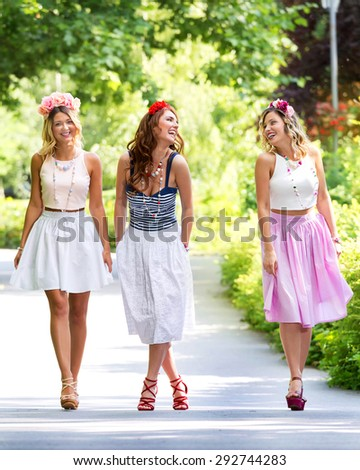 Beautiful pin-up girls with flowers in hair, posing in a green park. Soft focus - stock photo